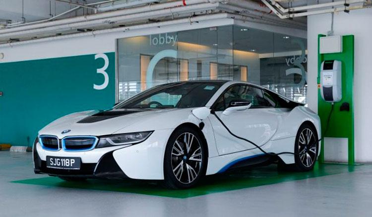 Imagen donde vemos un BMW i8 recargando sus baterías en una toma de conexión ubicada en el lateral izquierdo de este deportivo híbrido.