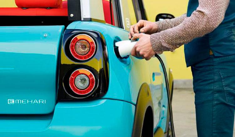 Imagen donde vemos una persona conectando el cargador del Citroën E-Mehari para recargar las baterías.