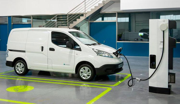 Imagen donde vemos una Nissan E-NV200 de color blanco recargan las baterías desde su toma de conexión frontal.