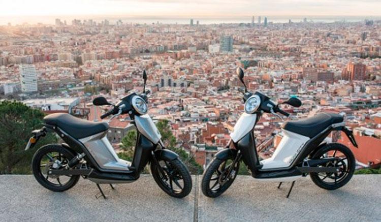 Imagen donde podemos ver los dos modelos de la Torrot Muvi, la City y la Executive, con una vista de fondo de la ciudad de Barcelona.