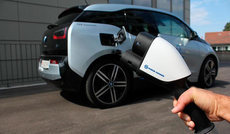Imagen donde podemos ver un cable de conexión HUBER+SUHNER y al fondo un coche eléctrico BMW i3.