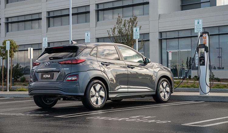 Imagen donde podemos ver un Hyundai Kona EV recargando sus baterías frente a un edificio de oficinas.