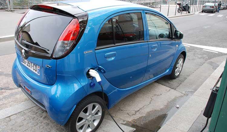 Imagen donde vemos un Peugeot iOn recargarndo sus baterías con la toma de conexión ubicada en el lateral derecho de la zona trasera del vehículo.
